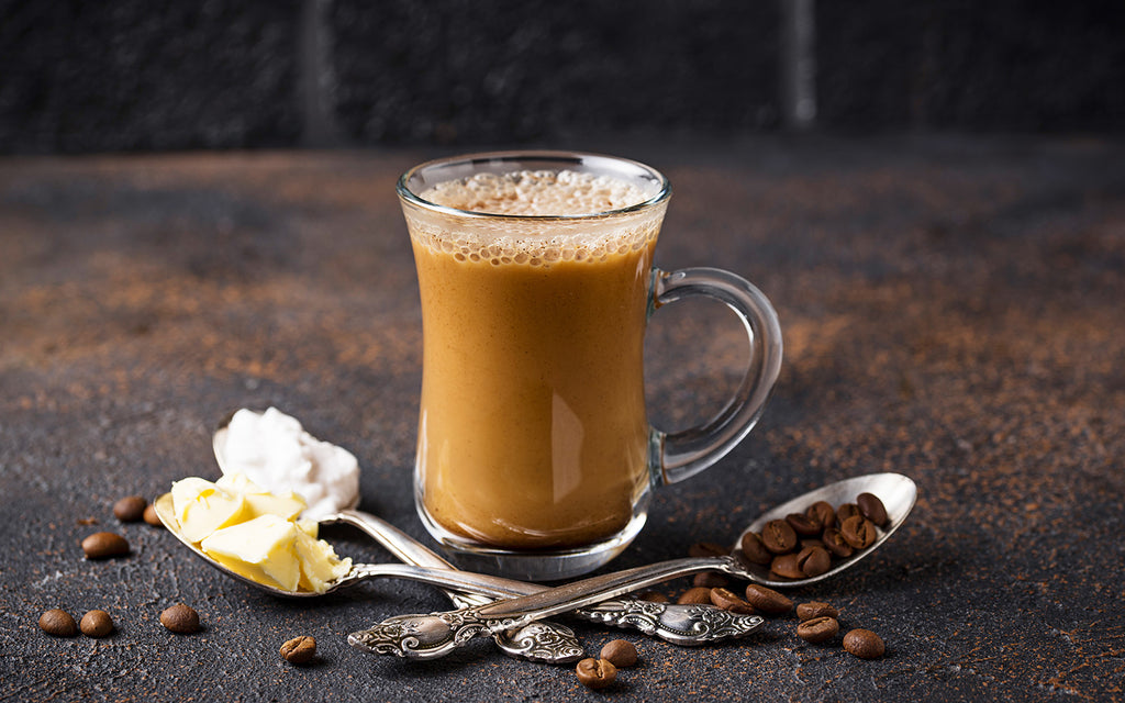 Bulletproof coffee UK: Coffee in a glass cup with spoons of coffee beans, butter and coconut oil