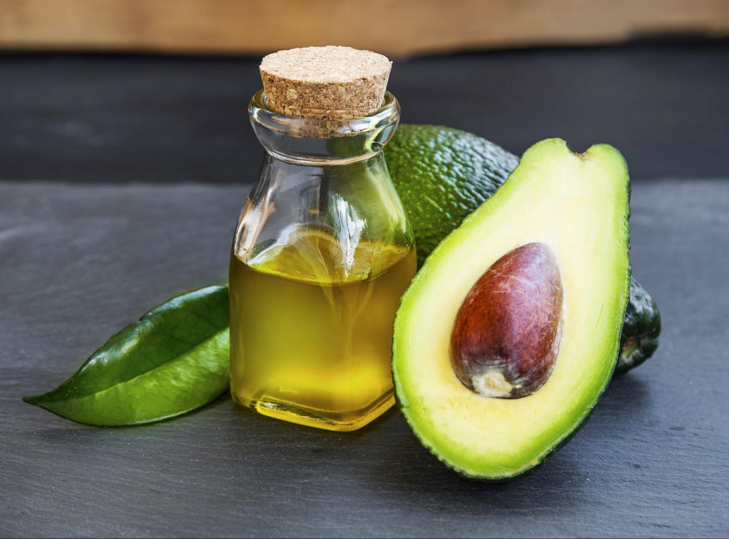 Avocado oil in a bottle with avocado fruit