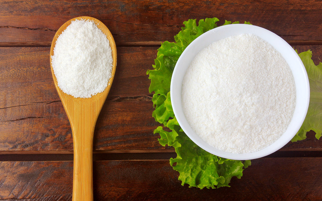 collagen powder in a white bowl and in a wooden spoon