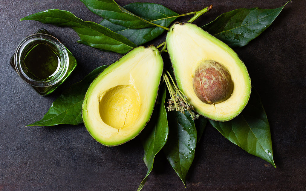 Avocado sliced in half on top of leaves and a bottle of oil beside it