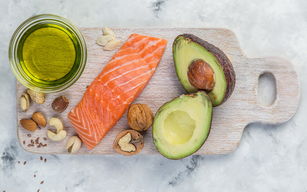 Cutting diet: Raw salmon, avocado, jar of oil, and nuts on a cutting board