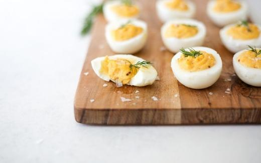 Keto Dill Stuffed Eggs in a wooden board