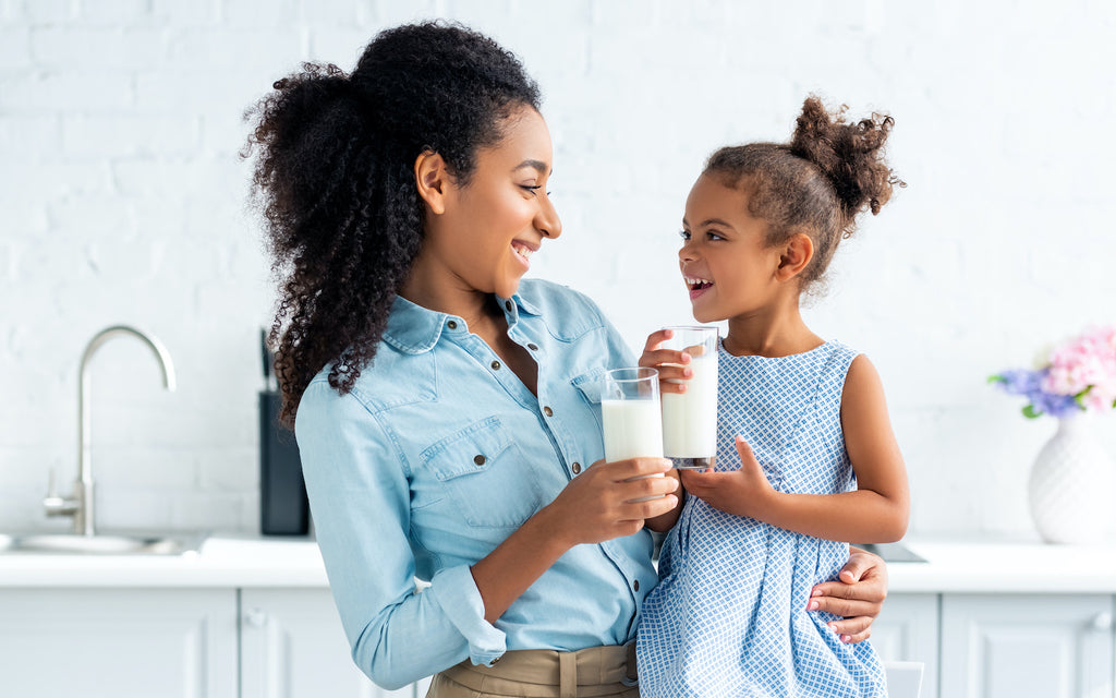 milk on keto: woman and a girl holding a glass of milk