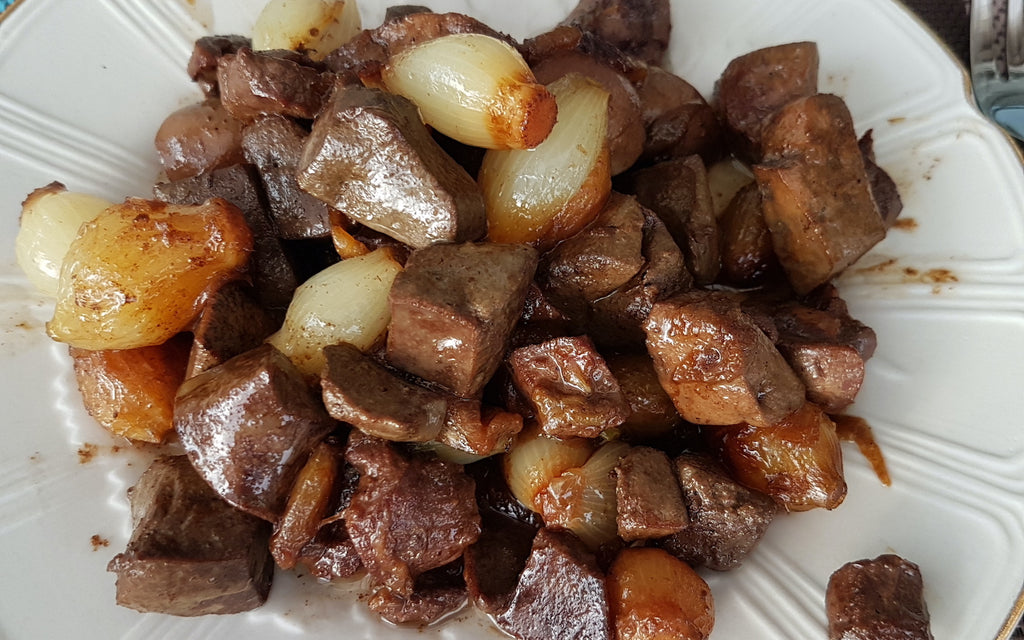 Kidney stew with onions on a white plate