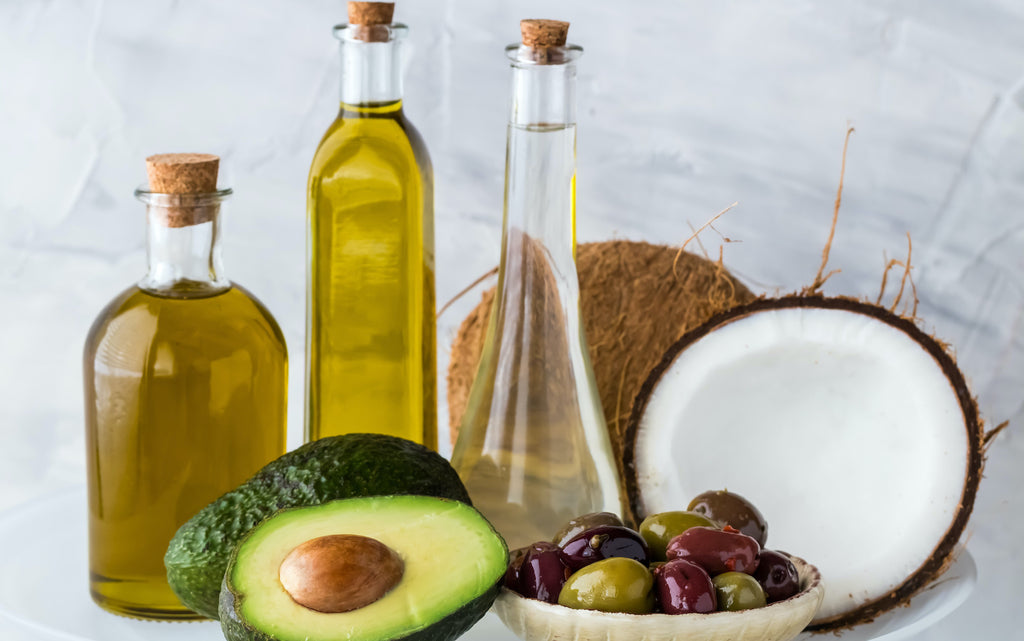 different kinds of oil with avocado, coconut, and grapes