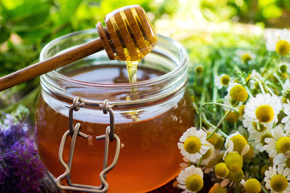 jar of honey placed outdoors