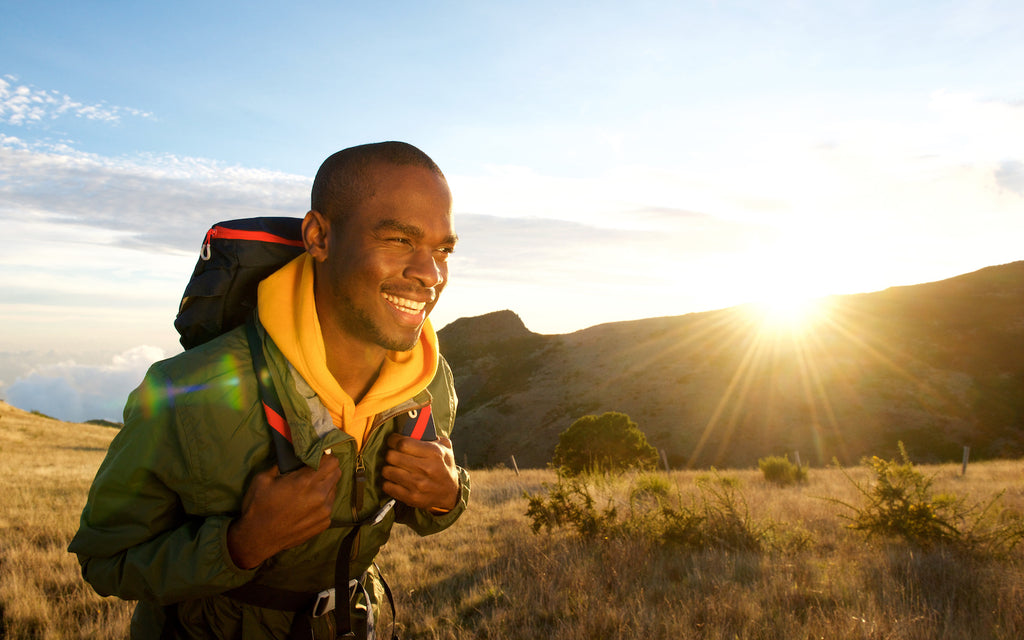 C8 MCT oil: Smiling man walking in the mountains while wearing a backpack