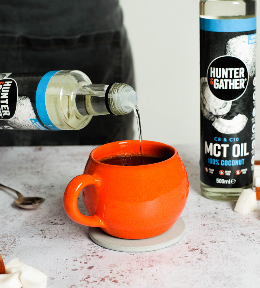 MCT oil being poured from the bottle into a cup of coffee
