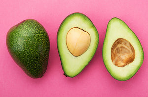 3 avocado halves on pink background