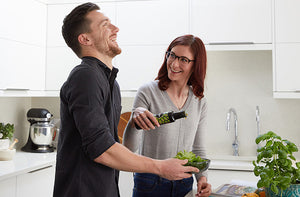 Two people in kitchen pouring avocado oil