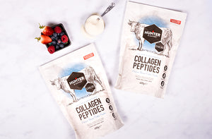Berries and collagen protein powder on white marble