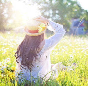 Lady sitting in sunny grassland with hat on