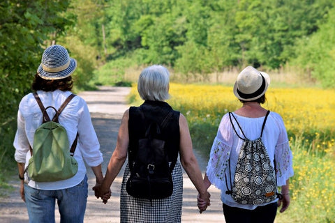 Three female seniors are holding hands walking in the woods. These seniors use Stirling CBD to reduce pain and inflammation.