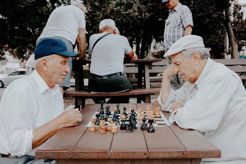 Older gentlemen playing chess in the park. Wearing shite shirts and white hats. These seniors use Stirling CBD for mental health.