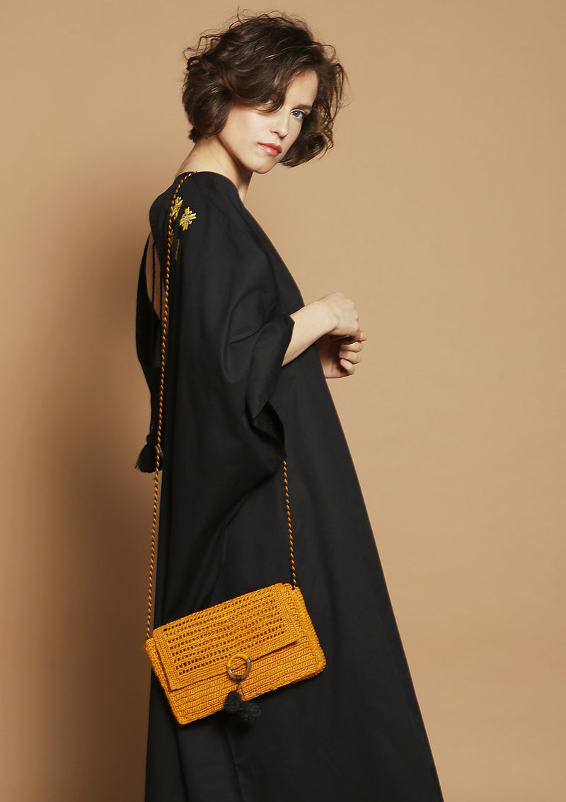 black beach dress with raffia clutch