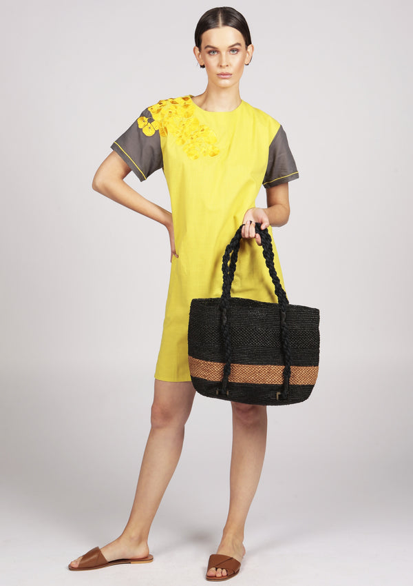 raffia beach bag with a yellow embroidered midi dress