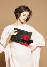 designer raffia clutch with pompom