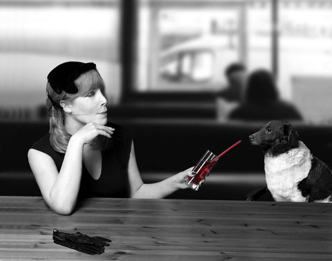 Black and white pic of woman and dog sitting at a bar. She is offering the dog a sip from a straw.