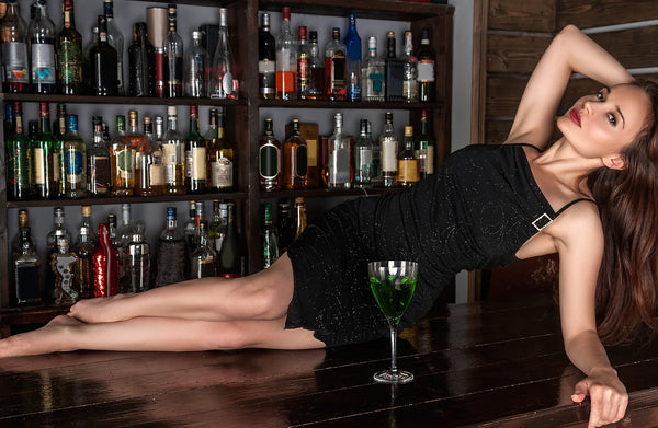 Young white woman in black cocktail dress lounging on a bar with a green drink.
