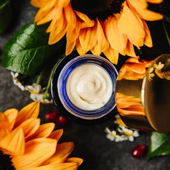 Ad Astra Nighttime Eye Cream emulsion, open, showing creamy white texture, on a bed of sunflowers.