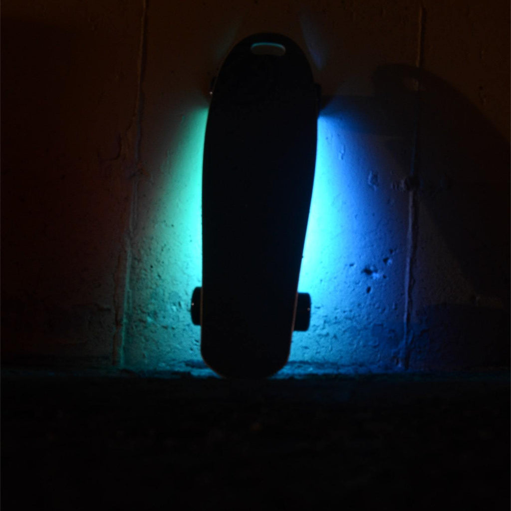 Atom B10 Electric Skateboard with lights leaning on wall