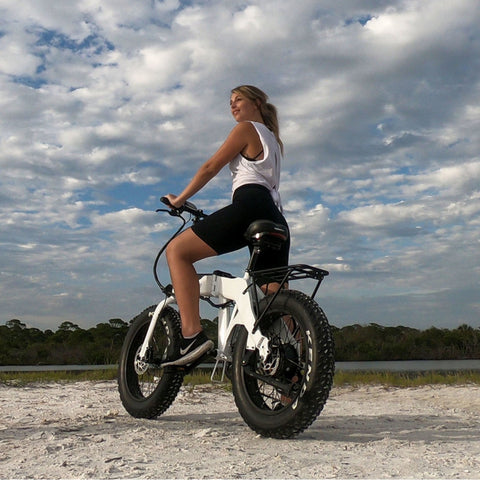 Jupiter Defiant Foldable Electric Bike rear view girl riding on beach