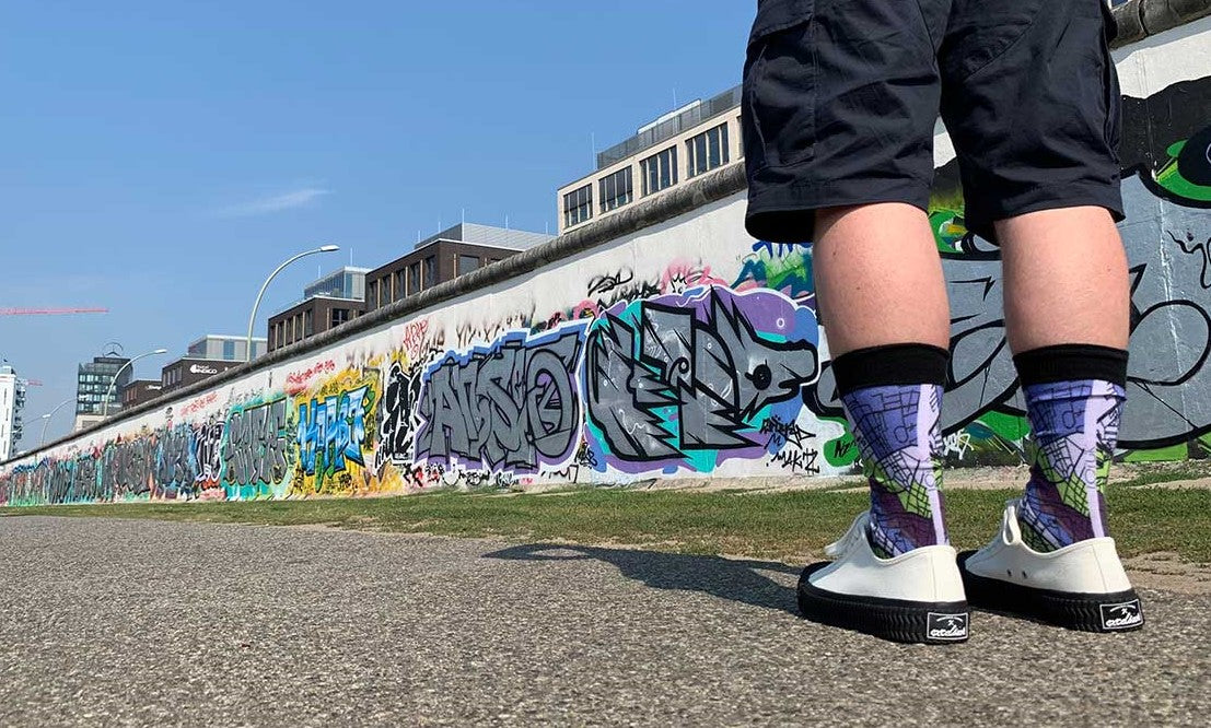 Man Wearing Berlin Map Socks At Berlin Wall