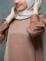 Girl wearing an oversized satin top with cuffed sleeves and a hijab