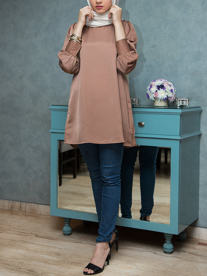 Girl wearing an oversized satin top with cuffed sleeves and a hijab paired with jeans