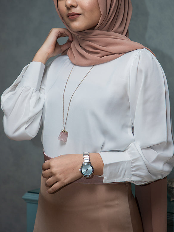 Girl wearing a white satin top with cuffed sleeves and a hijab
