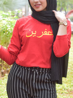 Red tshirt with name printed in arabic in yellow worn with head scarf and pinstripe pants