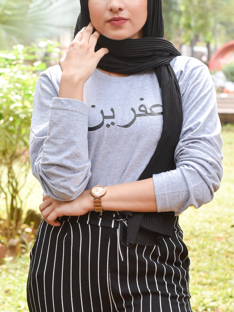 Grey tshirt with name printed in arabic in black worn with head scarf and pinstripe pants