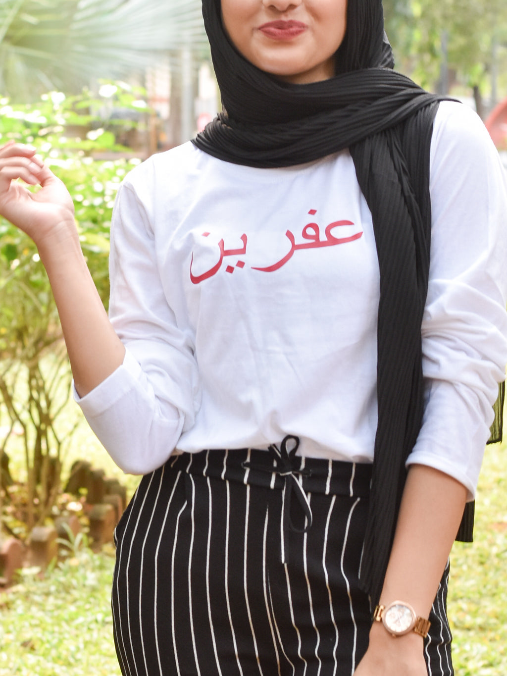 White tshirt with name printed in arabic in red worn with head scarf and pinstripe pants