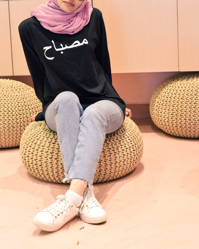 Black tshirt with name printed in arabic in white worn with head scarf and jeans