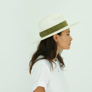 side profile of woman wearing white Panama hat with green band