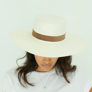 woman wearing white boater Panama hat with brown suede band