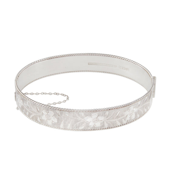 A modern, silver, engraved bangle with a beaded edge