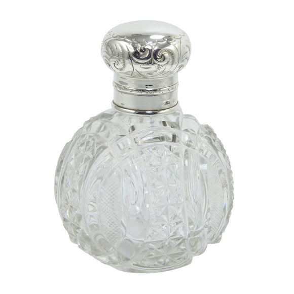 An Edwardian, cut glass, circular scent bottle with a silver lid