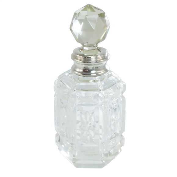 An early 20th Century, cut glass, hexagonal scent bottle with a silver mount & glass stopper