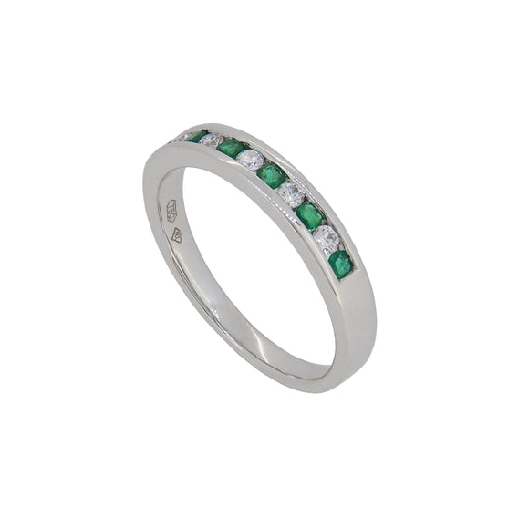 A modern, 18ct white gold, emerald & diamond set half eternity ring