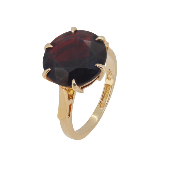 A modern, 9ct yellow gold, garnet set single stone ring