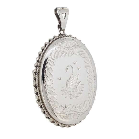 A modern, silver, oval, rope edged locket engraved with an image of a swan