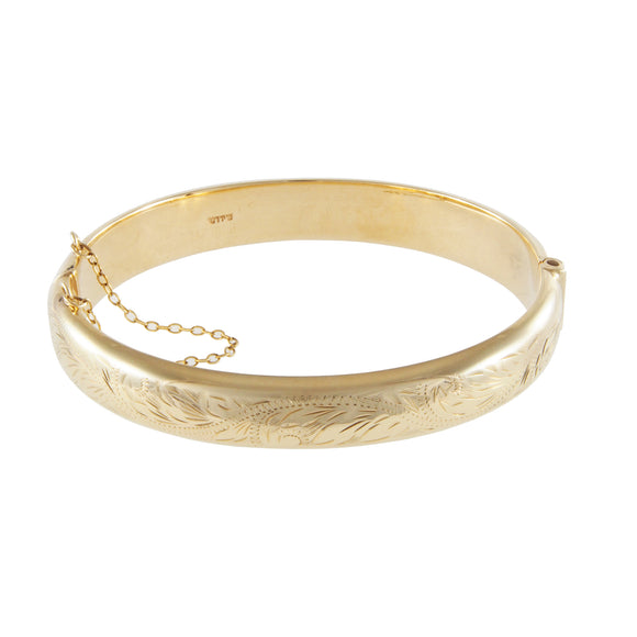 A modern, 9ct yellow gold, hollow, half engraved, hinged bangle