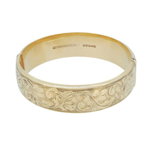 A modern, 9ct yellow gold, fully engraved, hollow, hinged bangle