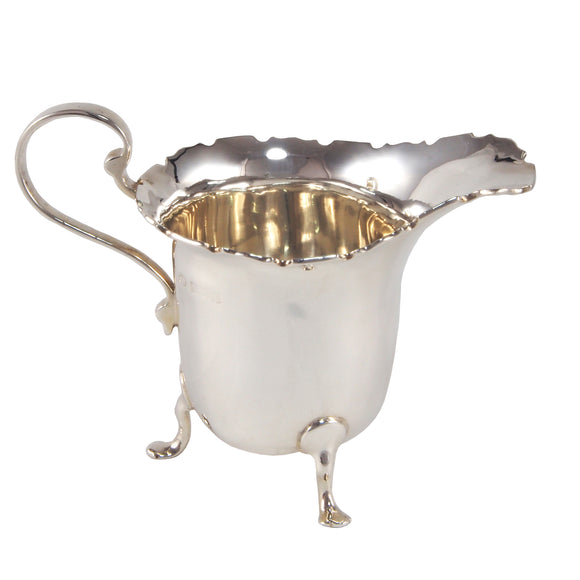 An early 20th century, silver cream jug on three feet