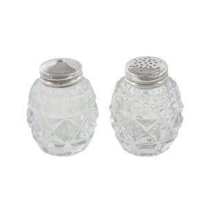 A pair of cut glass salt & pepper pots with silver lids