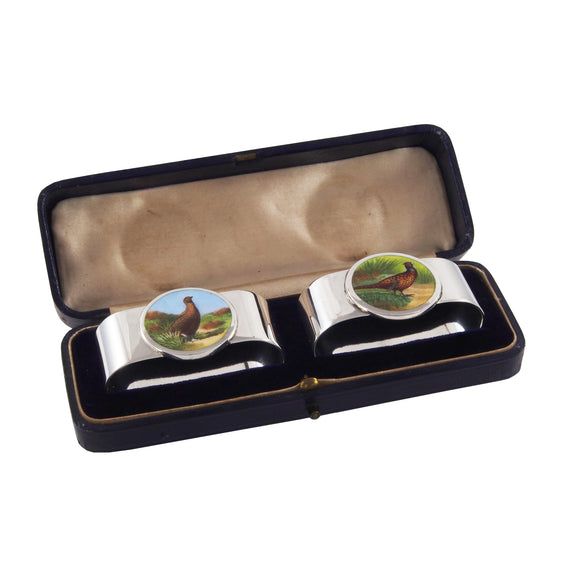 A pair of Edwardian, silver, oval napkin rings with enamel images of pheasants on the front & fitted case
