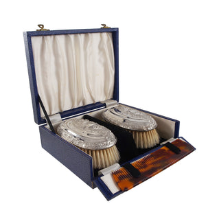 A pair of Edwardian, silver backed hair brushes, comb & fitted case