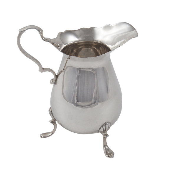 An Edwardian, silver cream jug on three feet