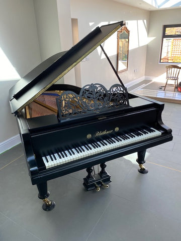 A fully restored Bluthner grand piano that was in a house fire